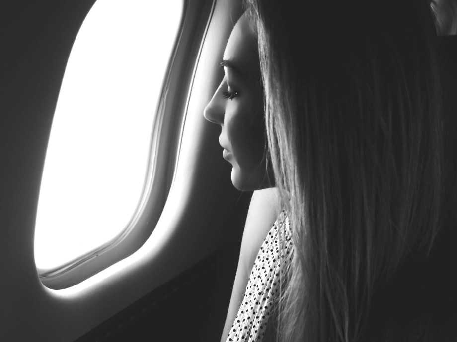 woman looking into the window in a private jet